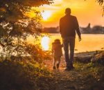 young man walks son out to lake at sunrise